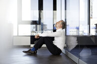 Businessman sitting on the floor in office with closed eyes - RBF06349