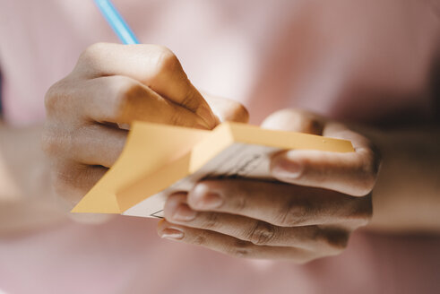 Woman writing with pen on adhesive notes - KNSF04064