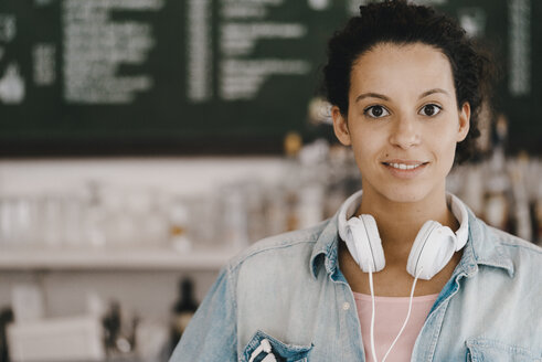 Young woman with headphones, working in coworking space - KNSF04088