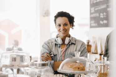 Woman with headphones standing in coffee shop with arms crossed - KNSF04091