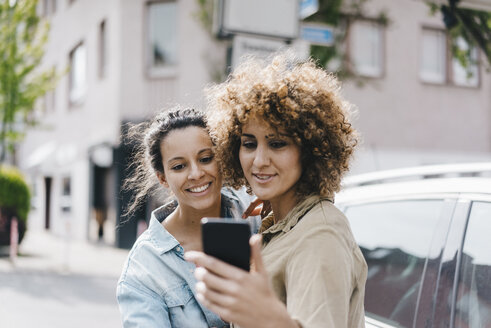 Best friends taking selfies with a smartphone in the city - KNSF04124
