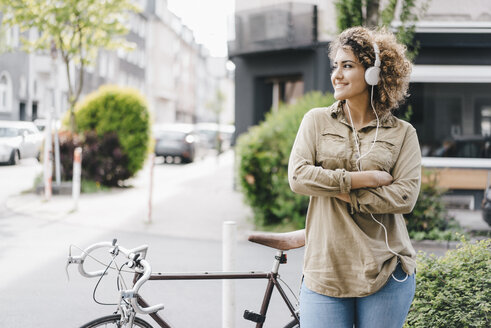 Woman in the city listening music with headphones - KNSF04139