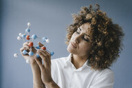 Female scientist looking at molecule model, looking for solutions - KNSF04157