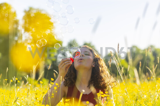 Young woman making soap bubbles - SARF03805