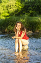Young woman sitting on stone, river - SARF03808