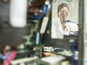 Female technician working with microscope in research laboratory - CVF00880