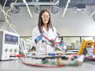 Female technician working in research laboratory, developing drone - CVF00886