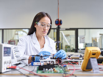 Female technician working in research laboratory, connecting plug of drone - CVF00889
