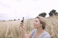 Woman with earphones on a field taking selfie with smartphone - KMKF00392