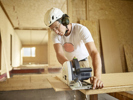 Worker with helmet sawing wood with circular saw - CVF00898