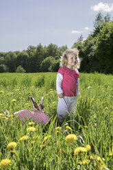Little girl with origami rabbit on meadow - PSTF00165