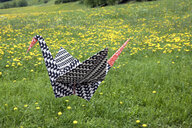 Origami crane flying over meadow - PSTF00168