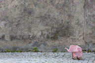 Origami elephant on cobblestones, concrete wall - PSTF00171