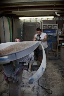 Mature man sawing a surfboard in his workshop - CUF34519