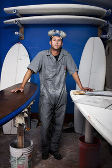 Portrait of a mid adult man and surfboards in his workshop - CUF34522