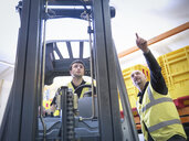 Trainer instructs male apprentice on forklift truck - CUF34579