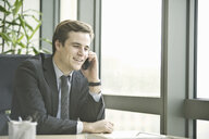 Young businessman talking on smartphone from office - CUF34591