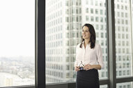 Portrait of young businesswoman looking out of office window - CUF34594