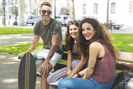 Portrait of three happy friends with skateboard relaxing in an urban park - WPEF00445