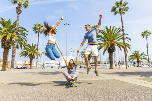 Carefree friends having fun with a skateboard on a promenade with palms - WPEF00451