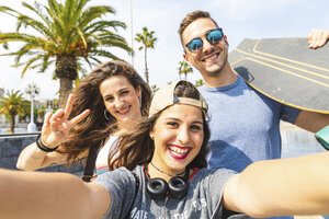 Selfie of three happy friends with skateboard - WPEF00457