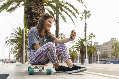 Happy teenage girl sitting on skateboard listening to music with headphones - WPEF00466