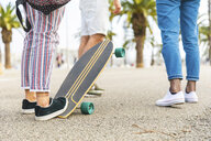 Close-up of friends with a skateboard on a promenade with palms - WPEF00469