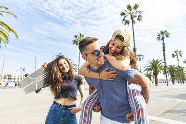 Happy friends with a skateboard having fun on a promenade with palms - WPEF00472