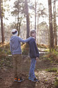 Twin brothers standing together in woods - CUF34634