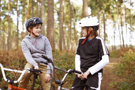 Twin brothers on BMX bikes chatting in forest - CUF34658