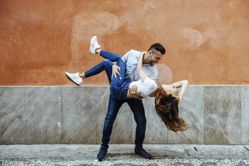 Carefree couple in love in front of a wall outdoors - JSMF00307