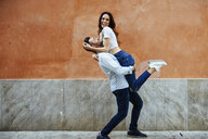Carefree couple in love in front of a wall outdoors - JSMF00310