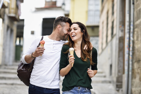 Happy tourist couple with ice cream cones in the city - JSMF00319