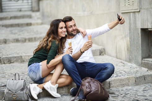 Tourist couple with ice cream cones in the city taking a selfie - JSMF00322