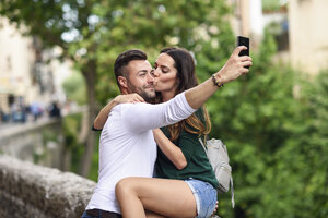 Couple in love in the city kissing and taking a selfie - JSMF00328