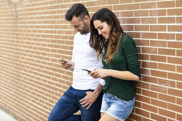 Couple looking at their smartphones at a brick wall - JSMF00337