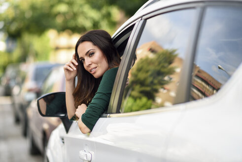 Young woman leaning out the window of her car in the city - JSMF00340