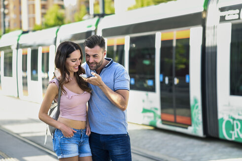 Couple using smartphone while waiting for tram at the station - JSMF00343