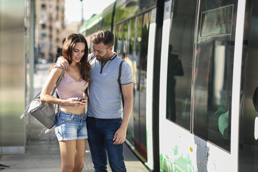 Couple looking at smartphone while waiting for tram at the station - JSMF00346