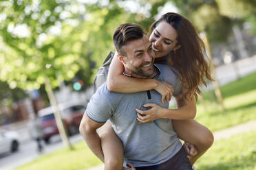 Happy man giving girlfriend a piggyback ride in park - JSMF00349