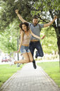 Carefree couple jumping in park - JSMF00355