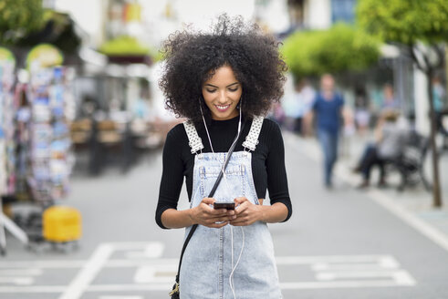Smiling young woman with earphones looking at cell phone - JSMF00358