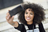 Portrait of smiling young woman taking selfie with smartphone - JSMF00364