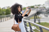 Smiling young woman with brown leather backpack standing on a bridge  taking photos with smartphone - JSMF00370