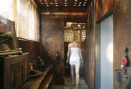 Back view of woman walking in  bathroom with corten steel wall cladding and ceiling light effects - REAF00342