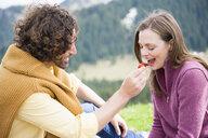 Mid adult couple sharing tomato on picnic, Wallberg, Tegernsee, Bavaria, Germany - CUF34713