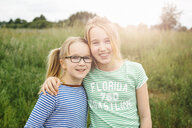 Portrait of eleven year old girl hugging sister in field - CUF34758