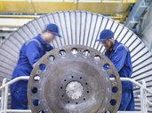 Engineers repairing steam turbine in workshop - CUF34965