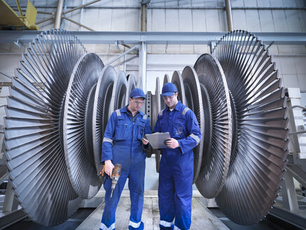 Engineers discussing notes in front of steam turbine in workshop - CUF34968