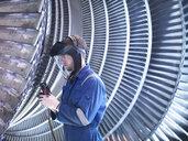 Engineer repairing steam turbine blade with grinder in workshop - CUF34971